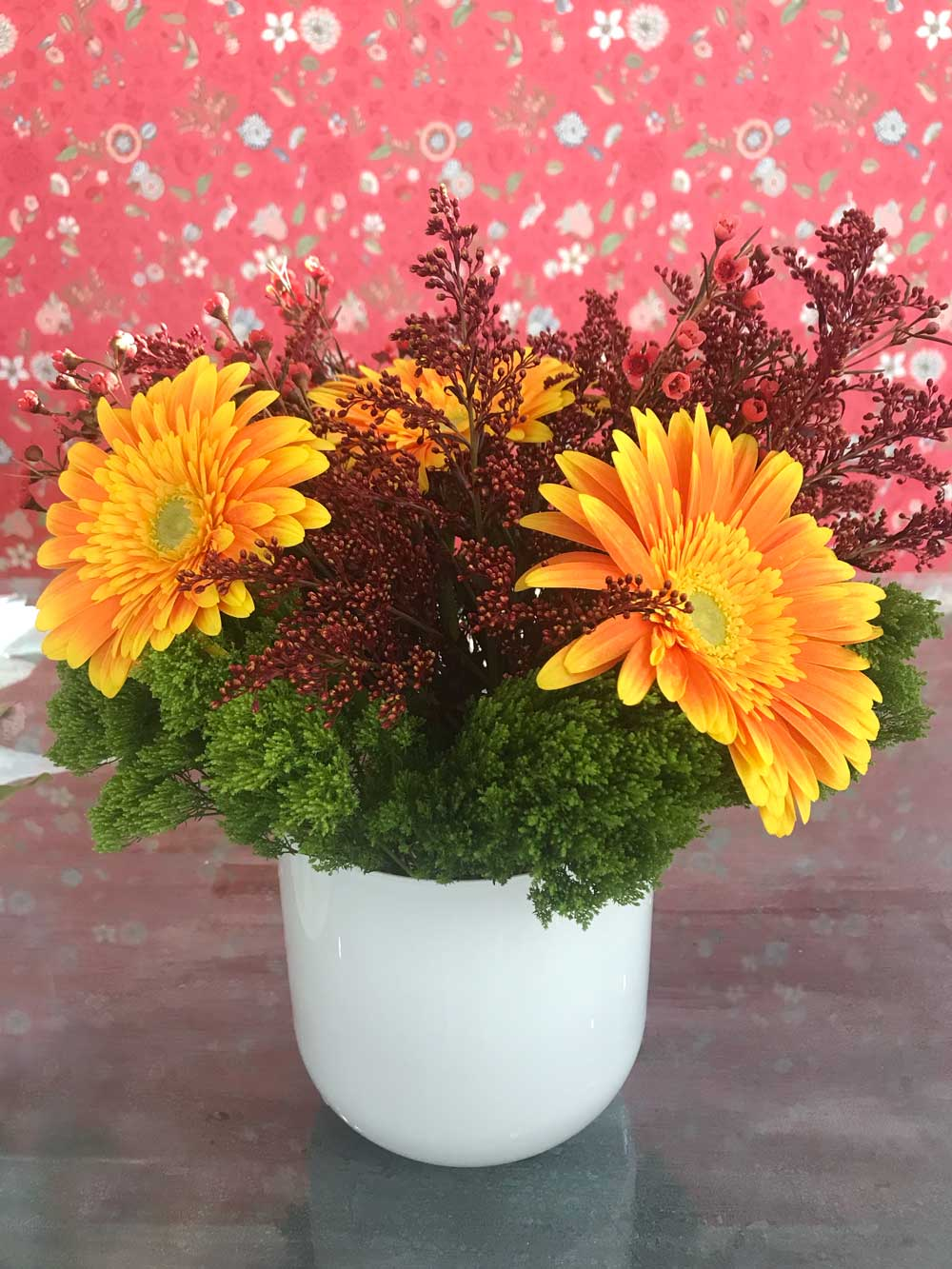 fresh flower arrangement in colors of burgundy, yellow and green in white vase