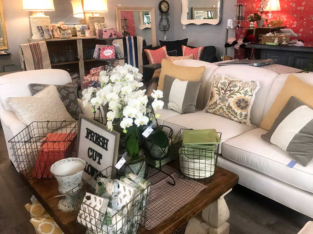 image of the store interior with couches, white fresh flower arrangement and assorted gifts and home decor
